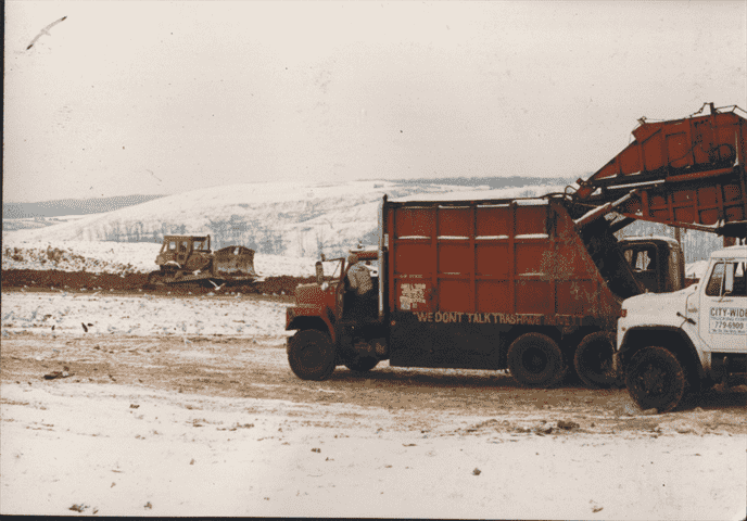 Rear load trucks and a landfill in a snow storm